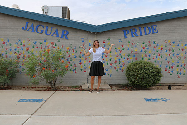 "a woman stands with her arms up; behind her, a wall covered in colorful handprints reads ""Jaguar Pride"""