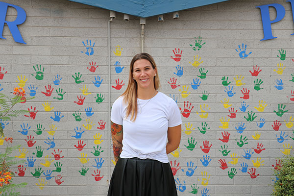a woman smiles as she stands with her back to a wall covered in colorful handprints