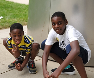 Two young brothers, getting ready to sprint race, squat for a quick photo at a park outside of Chicago.