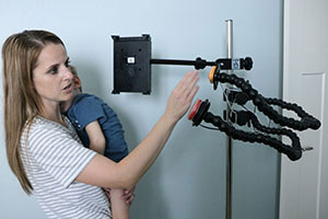A young woman, holding toddler son, taps a switch that is mounted to a pole