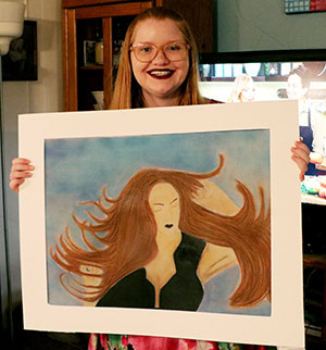 17-year-old girl holds up a sample of her artwork.
