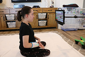Teenage girl, sitting on the floor, stares at an electronic table that is mounted to a pole.