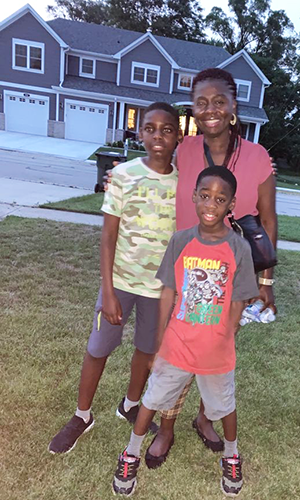 Mom poses with her two young sons outside a home in Chicago.