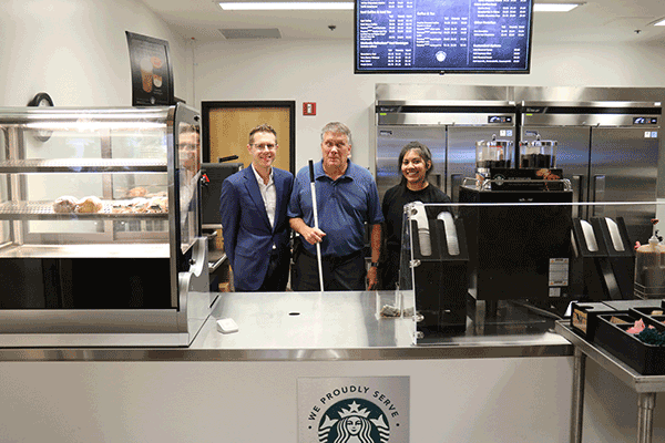 two men and a woman stand behind a counter with the Starbuck's logo on the front