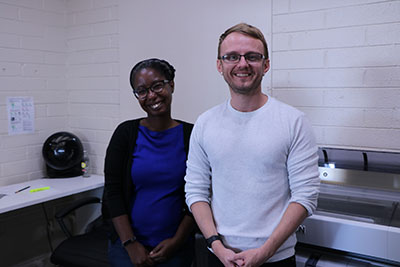 a woman and man stand in front of a large printer