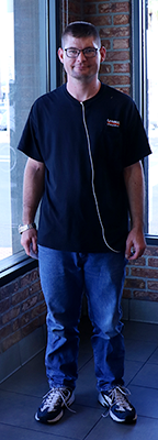 A man wearing glasses, a dark blue t-shirt, and blue jeans