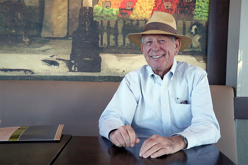 an older man wearing a hat and long-sleeved shirt smiles happily