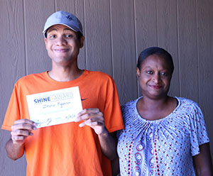 a young man wearing a baseball cap holds a certificate in front of him; an older woman stands beside him, smiling