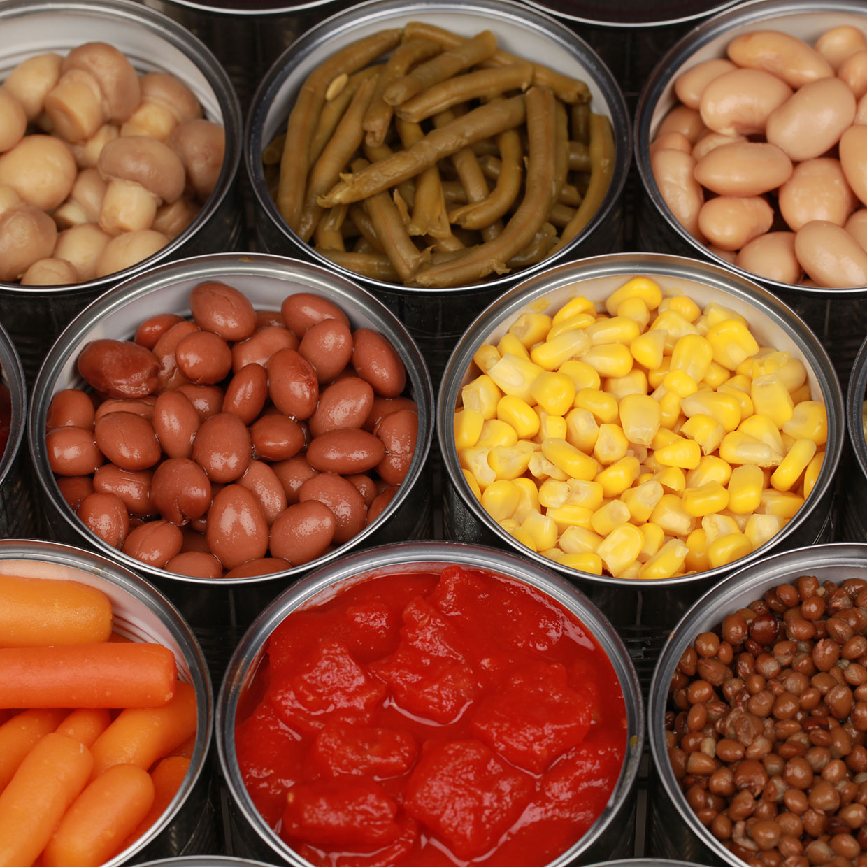 a group of opened cans of food containing fruits vegetables and legumes