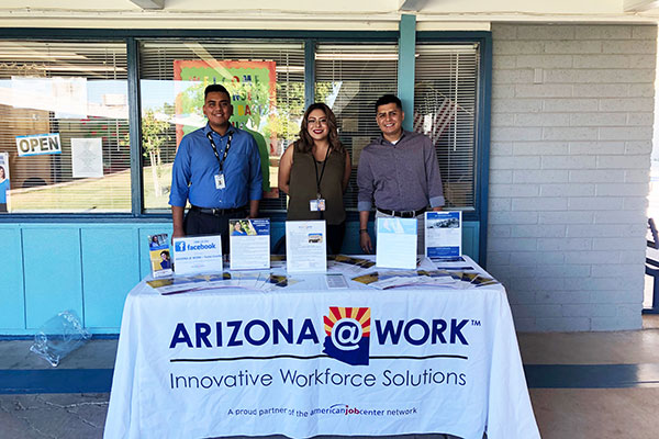 "two men and a woman stand behind a cloth-covered booth that reads ""ARIZONA@WORK Innovative Workforce Solutions"""