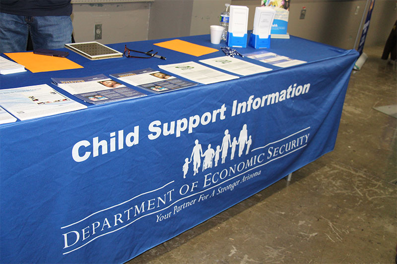 "a table is draped in a tablecloth with the words ""Child Support Information""; there are piles of flyers and pamphlets on the table top"