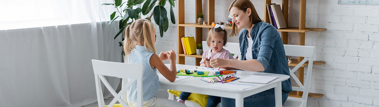 woman and two young girls sit at table making crafts