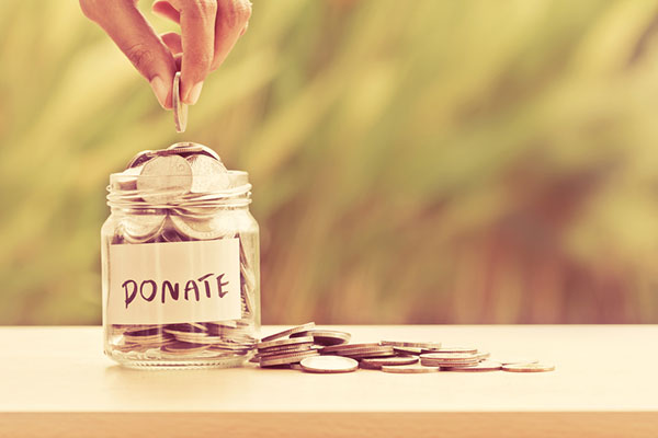 "a hand drops a coin into a jar labeled ""donate"""