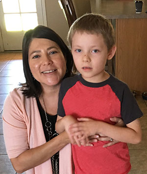Mom crouching down with her arms around her six-year old son.