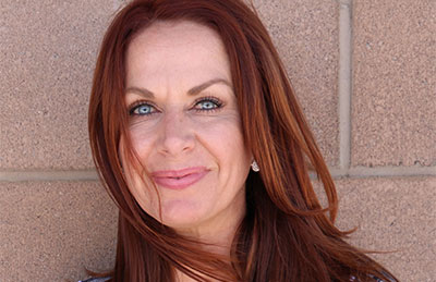 a woman with red hair and blue eyes smiles