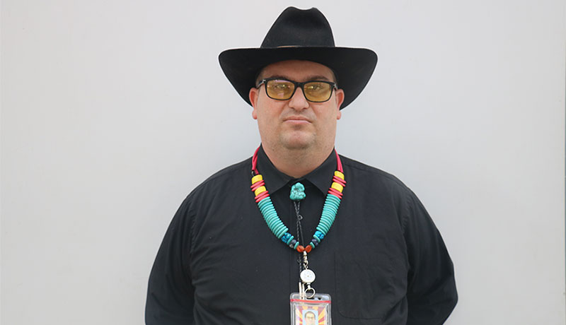 an in black shirt and cowboy hat standing against white wall