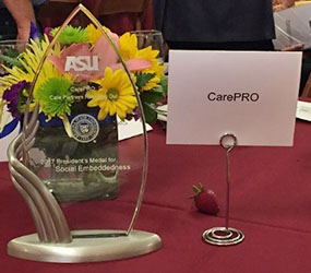 picture of a glass award inscripted with 'ASU' next to a placard with the words 'CarePRO'