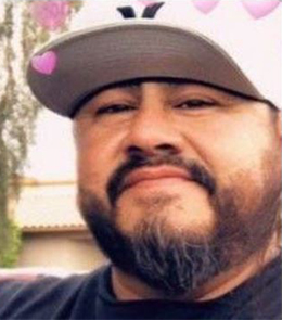 A Hispanic man with brown eyes and a black beard is wearing a white baseball cap