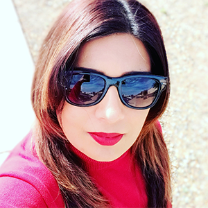 a young woman with long, brown hair is wearing sunglasses and a red blouse