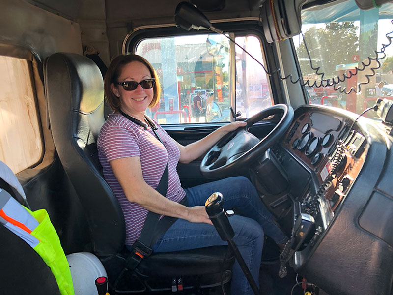 a woman sitting in the driver's seat of a large vehicle is smiling; a large steering wheel and many controls are visible