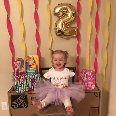A toddler in a pink tutu sits surrounded by birthday cards, signs, a balloon and streamers