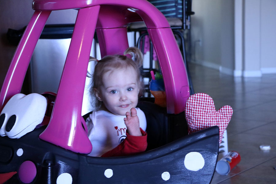 A toddler girl sits in a toy car with her foot sticking out of the window. The toy car is in a house on a tile floor.