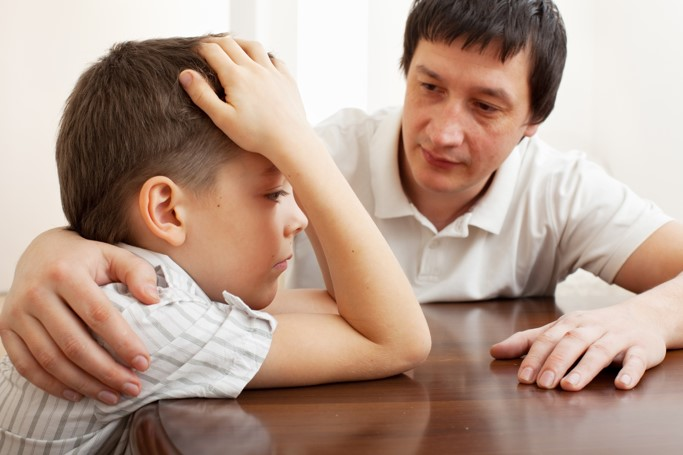 Man embraces boy while both are seated at table