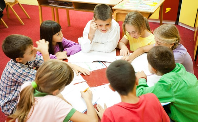 Children sit around a table in a classroom, while drawing in their books