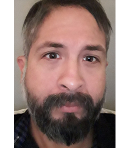 A Hispanic male with brown eyes, black hair, mustache and beard.