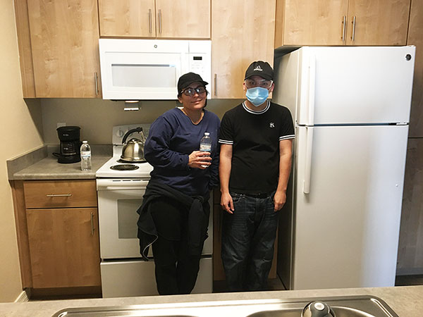 Mother and adult son stand next to the refrigerator in the kitchen of their new apartment home.