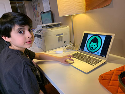 a young boy looks towards the camera while using his laptop