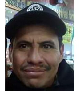 A Hispanic male with brown eyes, black hair and mustache.
