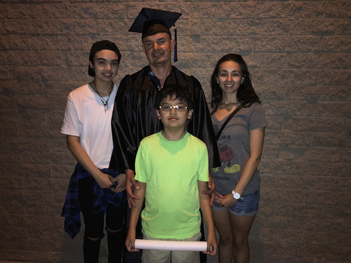 man in graduation cap and gown surrounding by three children