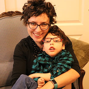 Sitting in an easy chair, a mother cuddles her five-year-old son.