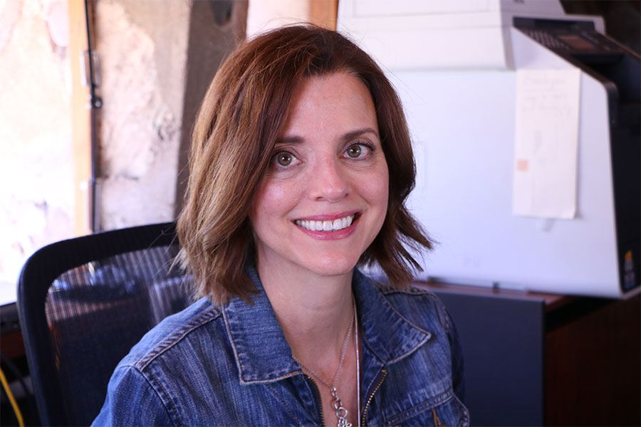 Head shot of a young woman with short brown hair wearing a denim jacket looks straight at the camera and smiles.