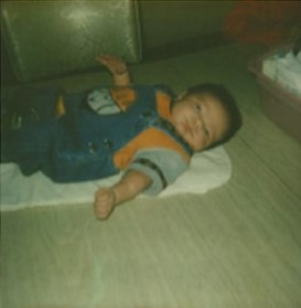 Infant boy lying on his back on the floor