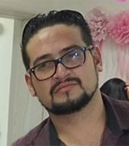 A Hispanic male with brown eyes, black hair, mustache and beard, wearing eye glasses.