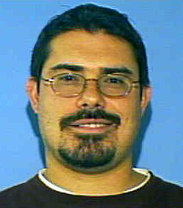 A white with man short, black hair, brown eyes, and a black goatee is wearing glasses and a black t-shirt.