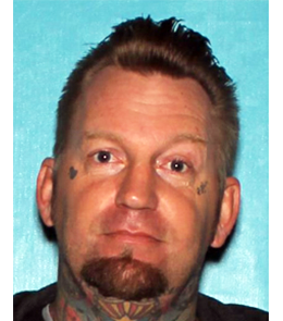 A white male with blue eyes, blonde hair, goatee, tattoos under each eye and on throat