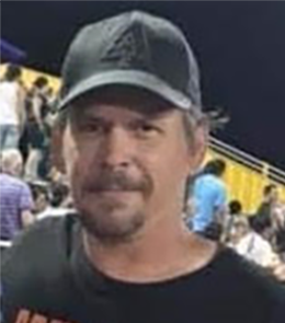 A White male with brown eyes, brown hair, mustache and goatee.