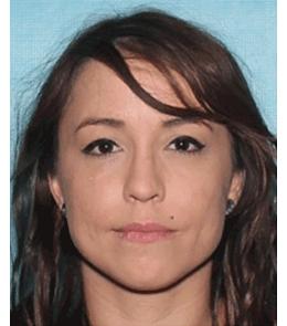 A Hispanic woman with brown eyes, brown hair, pierced ears, mole above left upper lip