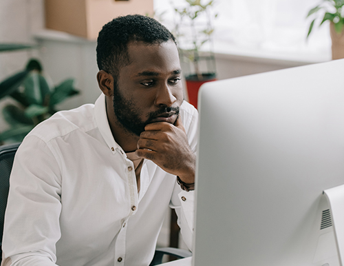 Man working thoughtfully on a computer.