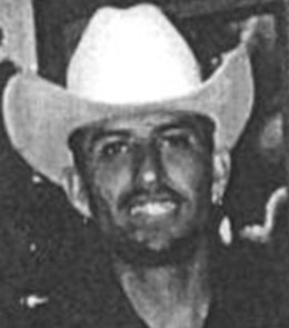 A Hispanic man with brown eyes, brown hair, and a goatee is wearing cowboy hat and a black t-shirt.
