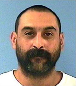 A Hispanic man with buzzed, black hair, brown eyes, and a thick, black beard is wearing a white t-shirt