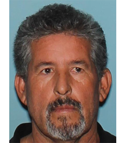 Hispanic man with brown eyes, short, graying, brown hair, and a goatee wearing a black collared shirt