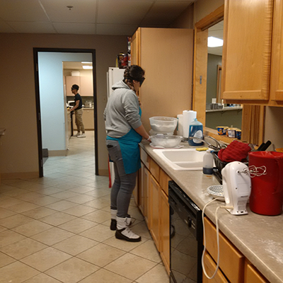 young woman is blindfolded, standing at kitchen counter with various bowls and cooking ingredients before her