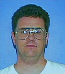 A Caucasian man with brown eyes and short, brown hair is wearing large glasses and a white t-shirt