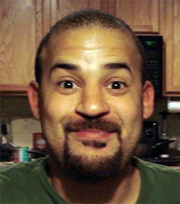A White male with brown eyes, black hair, mustache and goatee