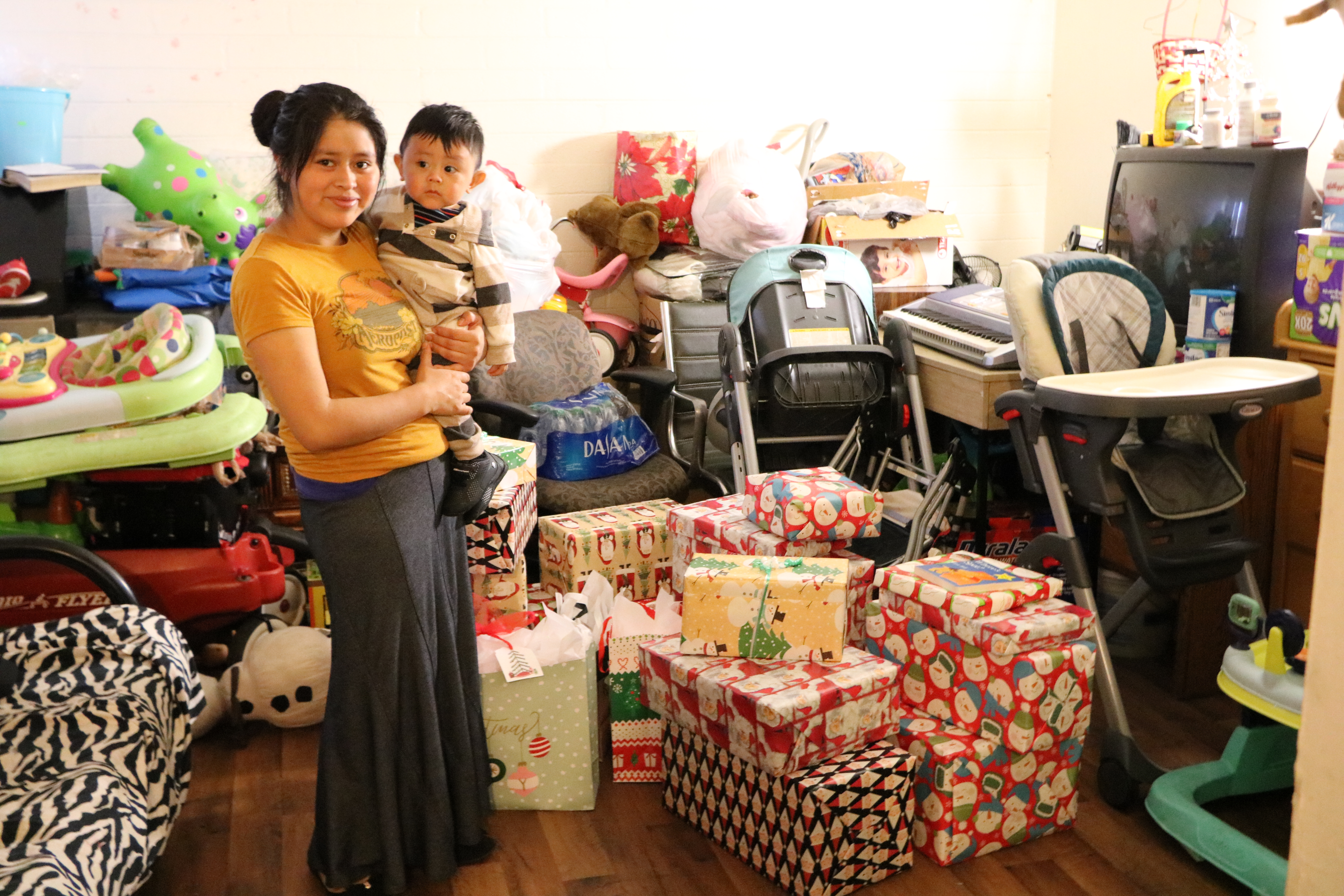 Mother and toddler stand in front of a pile of wrapped gifts