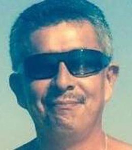 A Hispanic man with short, grey hair and a black mustache is wearing sunglasses.